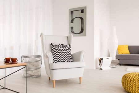 contrast: Light living room with simple table and comfortable armchair with decorative pattern pillow Stock Photo
