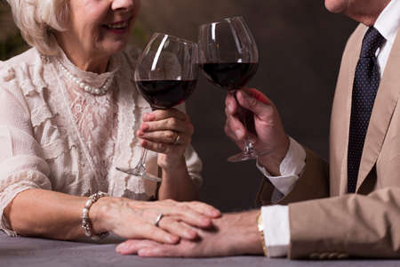 proposing a toast: Cropped picture of an old couple proposing a toast and holding hands Stock Photo
