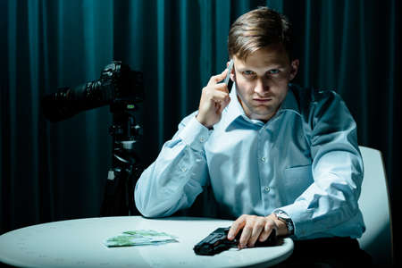 voyeur: Killer talking on cellphone, holding gun, money lying on a table Stock Photo