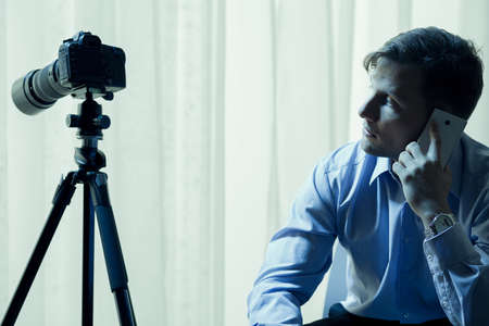 voyeur: Handsome man sitting beside a camera in dark interior Stock Photo