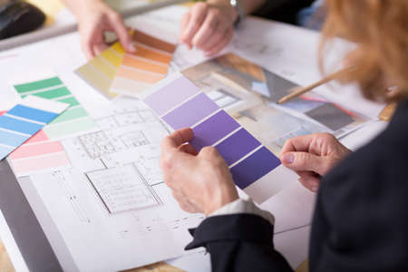 decorator: Close-up of technical drawings and colour samplers with a group of people choosing between them Stock Photo