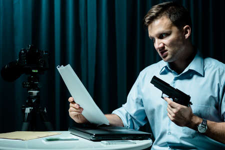 beside table: Angry man holding picture and gun, sitting beside table in dark interior