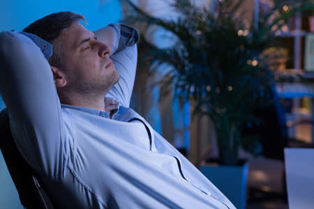night shift: Tired office worker sitting on chair at dark office Stock Photo
