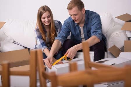 scotch tape: Shot of a young couple packing their things to boxes