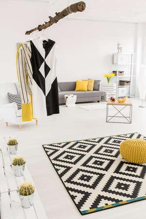 Geräumiger weißer Raum mit Musterteppich, einfachen Möbeln und stilvollen Dekorationen