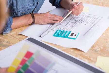 dibujo tecnico: Primer plano de una mesa de dibujo de madera aglomerada con muestreadores de dibujo, calculadora y de color técnicos, y un arquitecto medir algo usando la regla