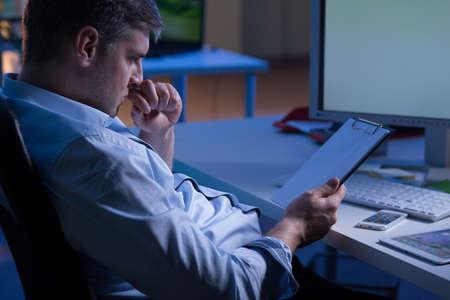 obrero trabajando: empleado de oficina ocupados trabajando en la noche, sentado al lado del escritorio