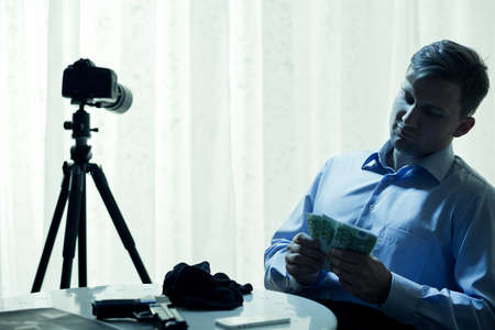 voyeur: Man sitting beside table counting money, gun lying on a table, camera in the background