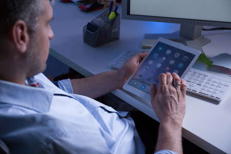 roster: Man addicted to work using his tablet sitting at dark office Stock Photo