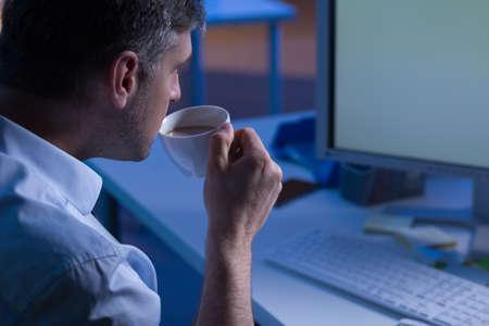 obrero trabajando: Primer plano de un ocupado oficinista beber café, trabajan por la noche