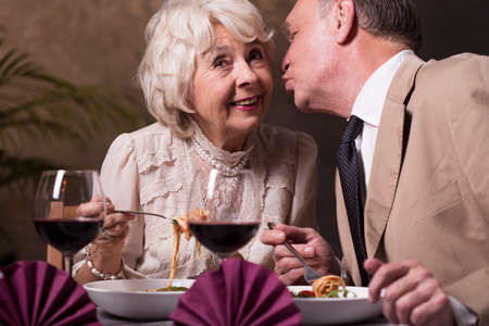 dinner date: Shot of a senior man kissing his wife on the cheek during a dinner