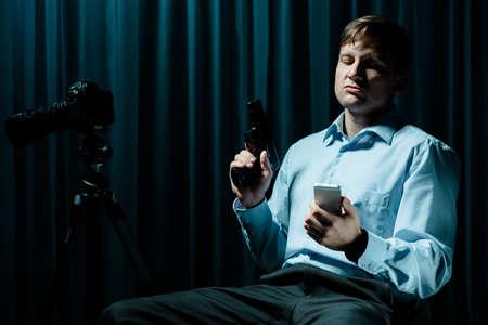 dark interior: Criminal sitting with gun and cellphone in dark interior Stock Photo