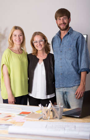 home business: Shot of three interior designers standing behind a desk full of papers and smiling at the camera