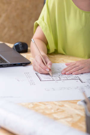 technical drawing: Close-up of a drawing table in an architects office with a young woman making some corrections on a technical drawing