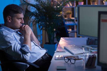 Fatigué employé de bureau assis au bureau de la nuit