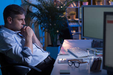 workaholic: Tired office worker sitting at office at night