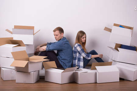 moving out: Shot of a young offended couple surrounded by boxes Stock Photo