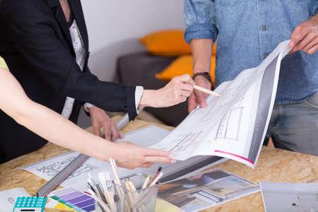 dibujo tecnico: Primer plano de una mesa de dibujo con los papeles y las muestras de color en �l, y los arquitectos que comentan en un dibujo t�cnico que se est�n llevando a cabo Foto de archivo
