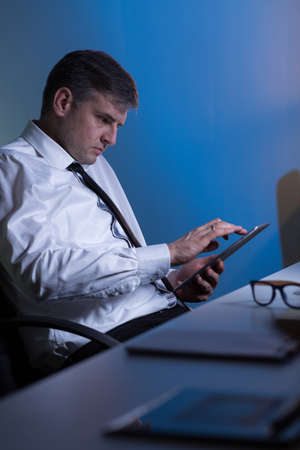 roster: Tired businessman sitting at his office at night Stock Photo
