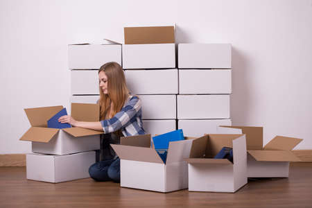 'young things': Shot of a young woman sitting on a floor and packing her things