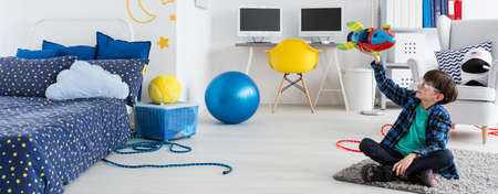boys playing: Boy playing with toy rocket in his room Stock Photo