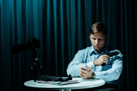 voyeur: Serial killer sitting in dark interior beside small table, holding gun and cellphone Stock Photo