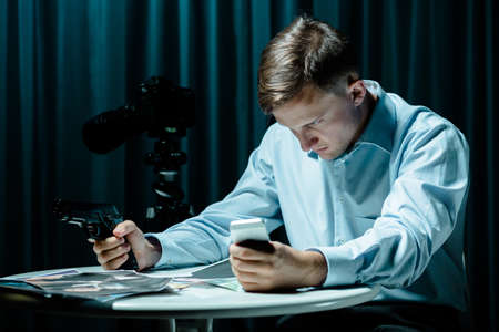 voyeur: Secret agent sitting in dark interior, holding gun and cellphone Stock Photo