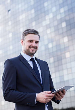Corporations: Handsome man with tablet on front of office