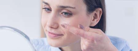 lentes de contacto: Captura de una mujer joven que intenta aplicar las lentes de contacto delante de un espejo