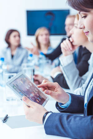 office presentation: Young pretty woman using new tablet during company business meeting. Talking about company strategy Stock Photo