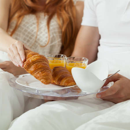 desayuno romantico: Pareja tiene desayuno romántico común en la cama