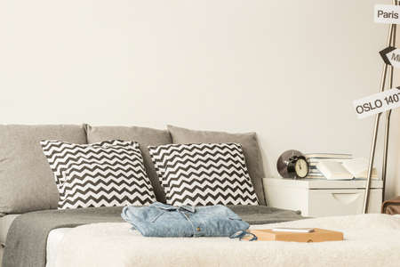 bedroom bed: Large bed decorated with patterned pillows in a modern bedroom, with white nightstand and personal items