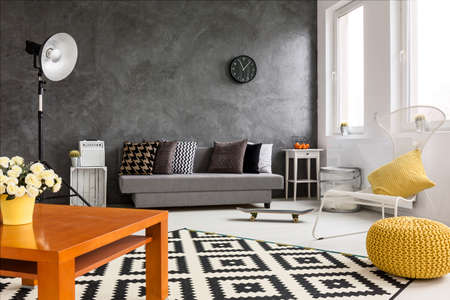 Grey and white living room with orange decorations making room cozy and bright Standard-Bild