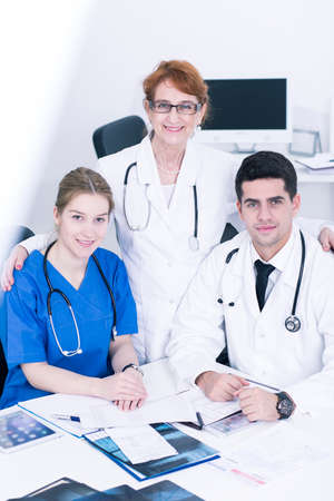 hardworking: Older smiling professor with her two hardworking residents. Embracing young woman and handsome young man in dusters Stock Photo