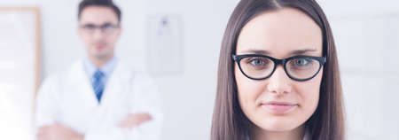 eye doctor: Shot of a young woman wearing glasses and her eye doctor standing in a background