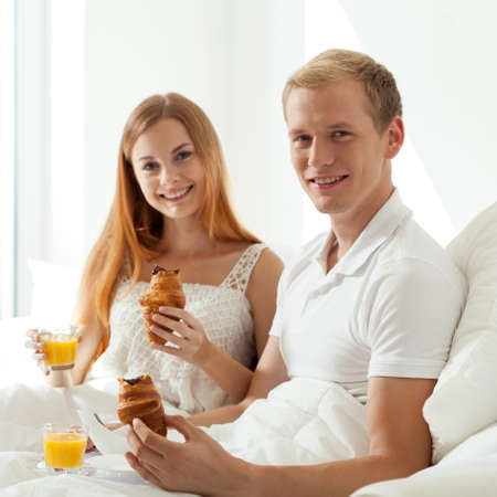 common room: Couple eating breakfast in bed at hotel room