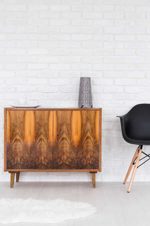 wood furniture: Loft arrangement- lacquered wooden commode on legs Stock Photo