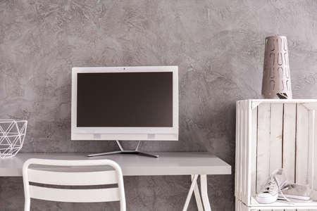 Ordenada oficina en casa moderna con escritorio blanco y nuevo equipo en el fondo de la pared gris