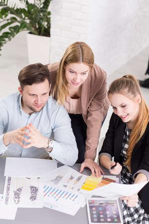 Tres jóvenes empresarios que trabajan en la pequeña empresa comprobar el progreso de empresa