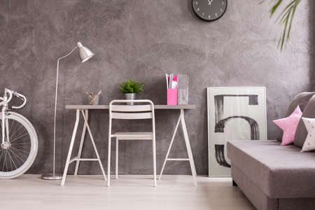 additions: Spacious living room with wooden parquet, grey walls and white additions. By the wall desk, sofa and bicycle
