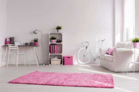 Tágas, elegáns stúdió, fehér falak és rózsaszín dekoráció. Kényelmes kanapé, szüreti kerékpár és íróasztal, a fal