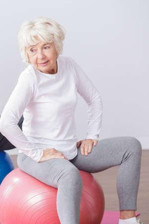 señora mayor: Retrato de una señora sonriente de edad en ropa deportiva, sentado en un ejercicio de pelota de color rosa Foto de archivo