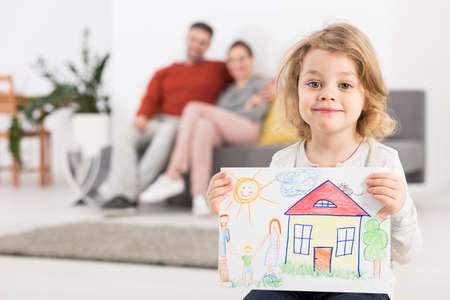 Photo of a smiling little girl holding a drawing with a house, with her parents sitting on a sofa in the blurry background