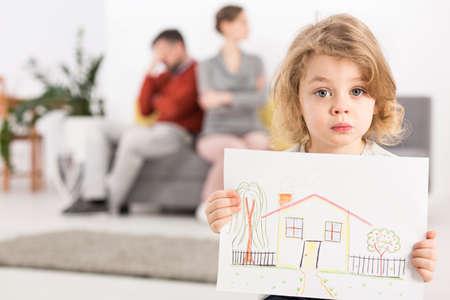 Trastorno del niño pequeño que sostiene un dibujo de una casa, con sus padres sentados en un sofá enojado en el fondo borroso Foto de archivo