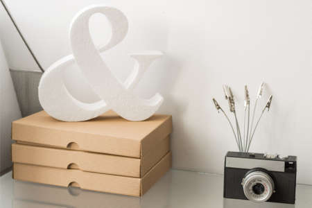 Shelf in a bright room, decorated with cardboard boxes, analogue photo camera and styrofoam decorative item Stock Photo