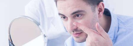 lentes de contacto: Disparo de un hombre joven que intenta aplicar las lentes de contacto delante de un espejo Foto de archivo
