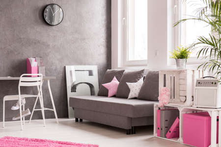 additions: Grey spacious living room with pink additions. Stylish shelf made of wooden boxes and comfortable sofa by the window