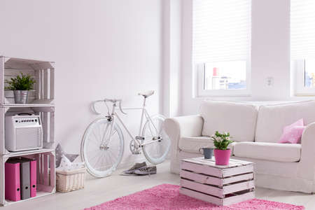 Modern designed lounge in white and pink. White comfortable sofa with coffee table made of old wooden box. By the wall vintage bicycle