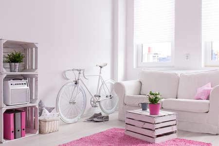 salon conçu moderne en blanc et rose. Blanc canapé confortable avec une table basse en vieille boîte en bois. Par le millésime mur vélo Banque d'images