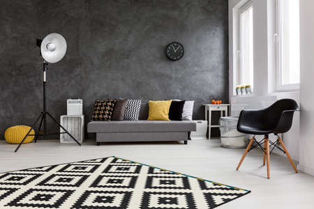 Modern living room with big space in the middle. By the wall comfortable grey couch with pillows and black chair